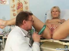 Mature Romana sits in a gynochair for an exam